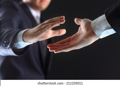 Photo of hands of business partners before handshake in black background