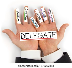 Photo of hands holding paper cards with DELEGATE concept words