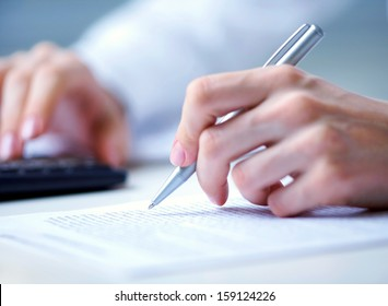 Photo of hands holding pen under document  and pressing calculator buttons