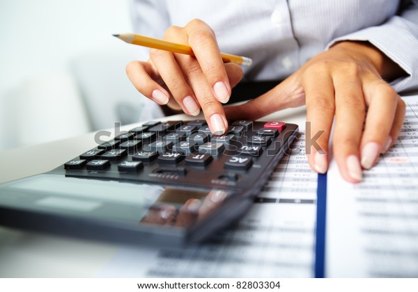 Photo of hands holding pencil and pressing calculator buttons over documents