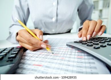 Photo of hands making notes with pencil and pressing calculator buttons