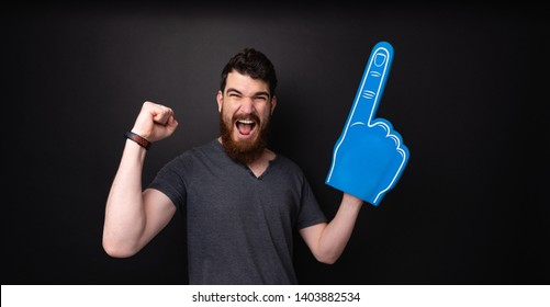 Photo of handsome bearded guy with big fan glove, screaming  and celebrating over  dark background