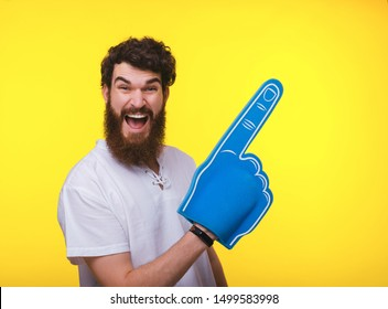 Photo of handsome bearded guy, with big fan glove, pointing away over eyellow background