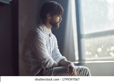 photo of a handsome bearded man with brown hair who sits on a chair in the studio with a ray of sunshine, he is wearing a white linen shirt and pants and looks away