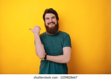 Photo handsome bearded man showing sign of cool, like it, close-up on yellow background
