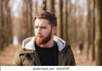 Photo of handsome bearded man standing in the forest. Look aside.