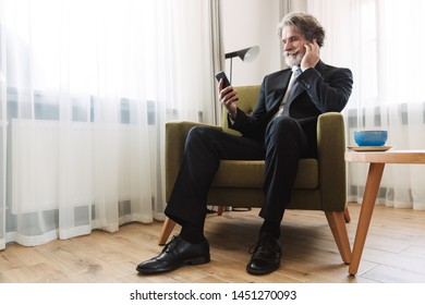 Photo of a handsome bearded mature grey-haired businessman posing indoors at home near window dressed in formal clothes using mobile phone sit on chair.
