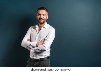 Photo of handsome cheerful man standing over dark blue background looking camera.