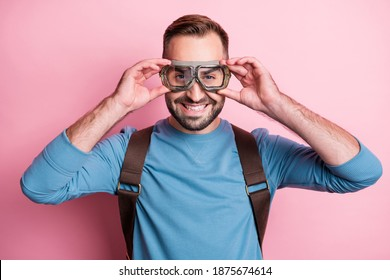 Photo of handsome cute young guy wear blue pullover arms glasses backpack ready to skydive isolated pink color background