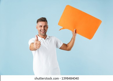 Photo of a handsome excited emotional adult man posing isolated over blue wall background holding speech bubble make thumbs up.
