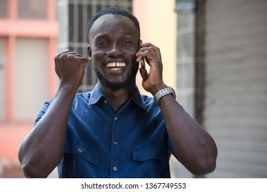 Photo of handsome excited man expressing surprise on face and gesturing while talking on the phone standing outside