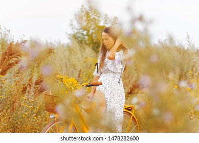 Photo of handsome girl in a vitage dress, standing on a bike, in a field of flowers