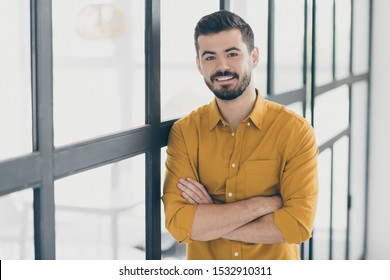 Photo of handsome guy with crossed hands standing in modern trendy interior apartments indoors near conference room window meeting colleagues