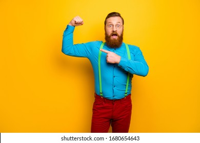 Photo of handsome guy raise fist arm indicating finger perfect shape biceps not believe fast success results wear blue shirt green suspenders red pants isolated yellow color background