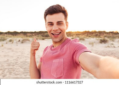 Photo of handsome happy young caucasian man make selfie by camera on the beach showing thumbs up.