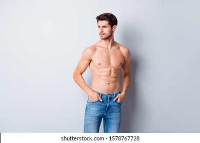 Photo of handsome macho man guy topless sporty torso metrosexual hot tender body holding hands in pockets looking side attentively wear jeans isolated grey background