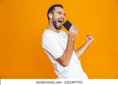 Photo of handsome man 30s singing while using earphones and mobile phone isolated over yellow background