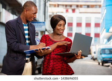 Photo of handsome man and beautiful woman as business partners outside holding in hand a computer and folder while smiling