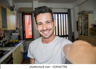Photo of handsome man taking a selfie at home smiling on the camera