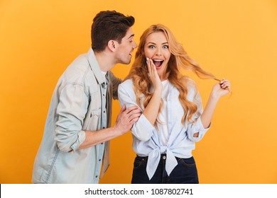 Photo of handsome man whispering secret or interesting gossip to young woman in her ear isolated over yellow background