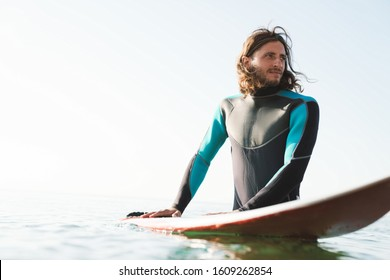 Photo of handsome masculine man in wetsuit using surfboard while working out in sea