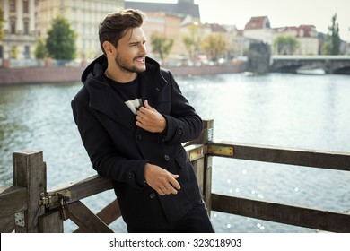 Photo of handsome smiling man in black coat in autumn scenery