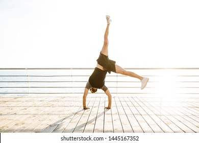 Photo of handsome strong young sports man at the beach near sea standing on arms hands make yoga cartwheel exercises.