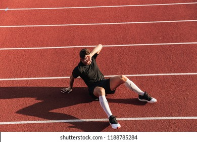 Photo of handsome strong young sportsman runner sitting outdoors.