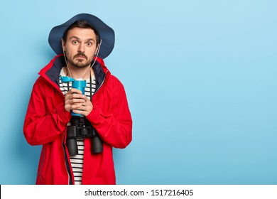 Photo of handsome unshaven man with mustache has expedition, stops for rest, drinks coffee from thermos, has surpirsed expression, uses binoculars for exploring surroundings, wears red jacket and hat