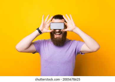 Photo of handsome young bearded emotional man standing over yellow wall background. Covering eyes with phone.