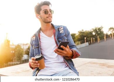 Photo of handsome young guy walking outdoors using mobile phone drinking coffee listening music.