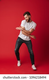 Photo of handsome young man dancing isolated over red wall background. - Shutterstock ID 1096218494