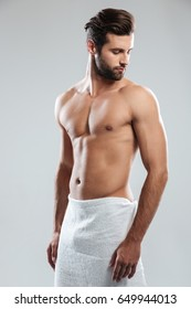Photo of handsome young man dressed in towel standing isolated over grey background. Looking aside.