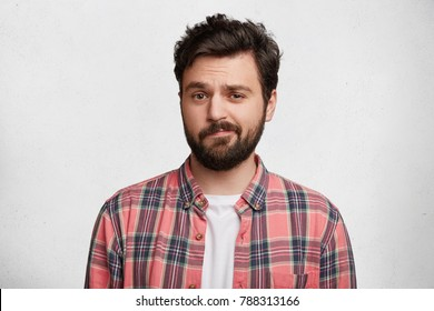 Photo of handsome young man with trendy hairdo and mustache, curves lips and frowns face in bewildermennt, isolated over white concrete background. Attractive male student in casual clothes.