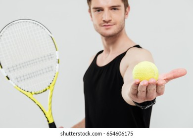 Photo of handsome young sportsman standing isolated over white background holding tennis ball and racket. Looking at camera.