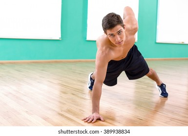 Photo of handsome young sporty man. Sportsman doing plank in sport club and looking at camera