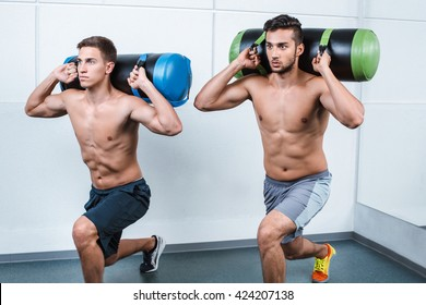Photo of handsome young sporty men. Sportsmen working out with sandbags
