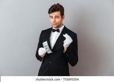 Photo of handsome young waiter standing isolated over grey wall background. Looking camera while holding money.