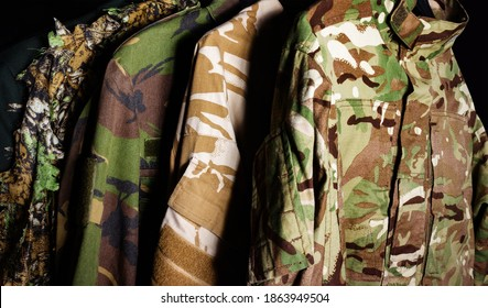Photo of a hanging military camouflaged jackets on black background.