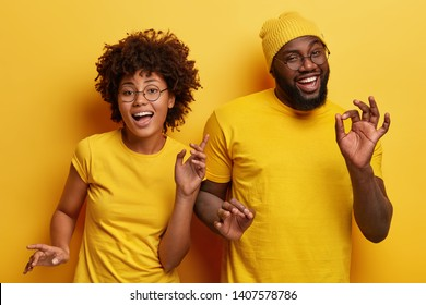 Photo of happy African couple dance together against yellow background, move body actively, show okay gesture, wear casual yellow t shirt, have fun during party. Monochrome. Feeling rhytm of music