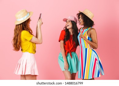 Photo of a happy amazing young three multiethnic girls friends posing isolated over pink wall background take a photo by mobile phone.