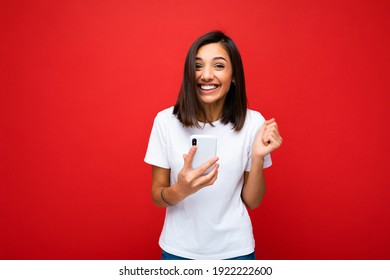 Photo of happy attractive crazy amazed surprised young woman wearing casual stylish clothes standing isolated over background with copy space holding and using mobile phone looking at camera