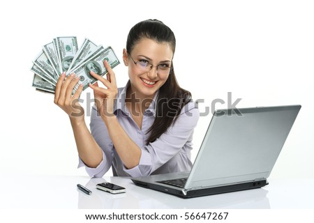 Photo of happy brunette woman in glasses with many dollars near laptop, isolated on white background