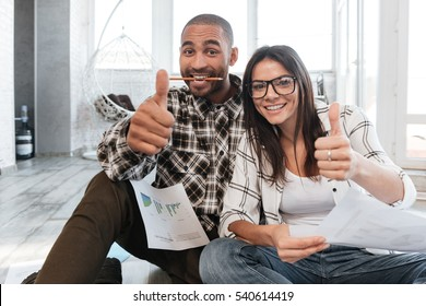 Photo of happy business partners in office working with documents on floor. Look at camera while making thumbs up gesture.