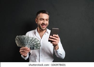 Photo of happy businessman isolated over dark black background using mobile phone holding money.