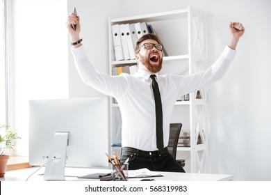 Photo of happy businessman standing in office near computer make winner gesture.