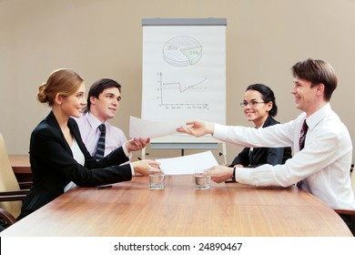 Photo of happy businesswoman passing over contract to partner while the others looking at them