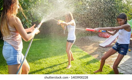 Photo of happy cheerful children wuth young mother playing with water guns and garden house. Family playing and having fun outdoors at summer
