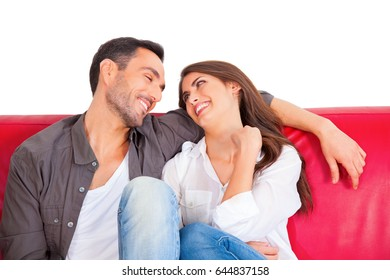 A photo of happy couple looking at each other. Loving young male and female partners are in casuals. They are sitting on sofa isolated on white background.