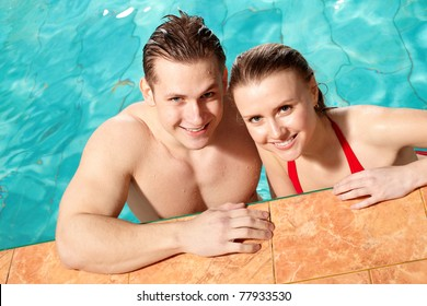 Photo of happy couple smiling at camera in swimming pool